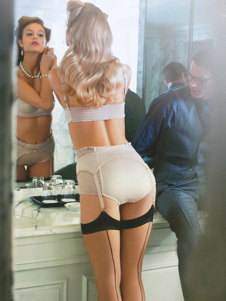 1 blonde woman ivory lingerie and stockings with garters putting on earings in front of mirror