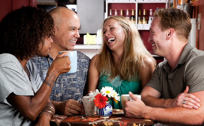Four adult friends meeting in a coffee house